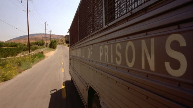 medium angle driving pov of brown bus on desert highway. camera mounted on left of bus reading federal bureau of prisons. neg cut. prison bus. - federal prison stock videos & royalty-free footage