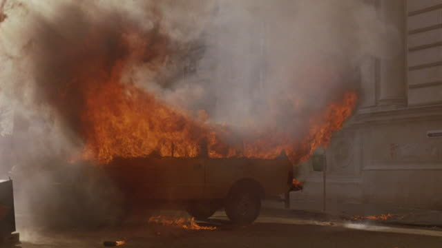 wide angle of a yellow truck or suv parked outside a building in a european city.  could be a bank, government office, or museum.  the suv explodes into fire and smoke. looks like a car bomb. - 1989 stock videos and b-roll footage
