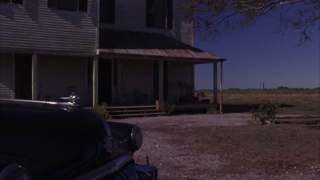 wide angle of a two story house from the early 1900s, maybe a farm or ranch house.  a late model car, could be between 1930s and 1950s, sits parked out front.  a field of grass in the distance. farmhouses. - ranch home stock videos & royalty-free footage