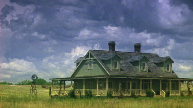 wide angle of ranch house in countryside or prairie. could be grasslands. windmill next to farmhouse. overcast sky. - prairie stock videos and b-roll footage