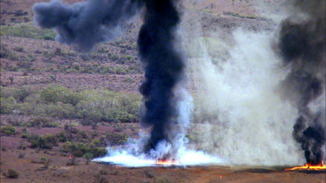 medium angle of desert covered in brush. see distant containers or items. see one explosion and black smoke. see second large explosion. pan up to see black plume. - container stock videos & royalty-free footage