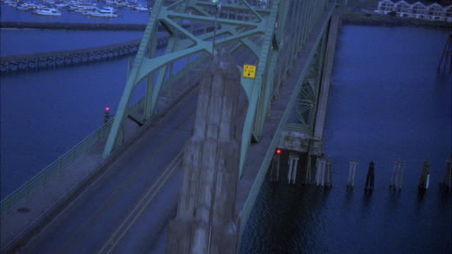TRACKING SHOT OF NAVY AND TAN FORD EXPLORER DRIVING OVER YAQUINA BAY BRIDGE. MARINAS AND NEWPORT, OREGON COAST VISIBLE.