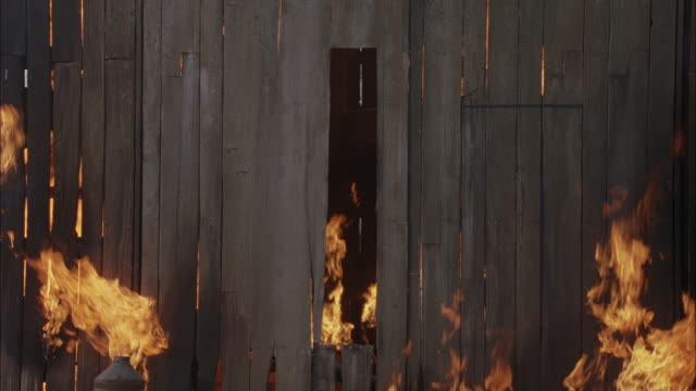 medium angle of wood wall of house or barn burning. see yellow and orange flames squeeze through cracks in wood boards to reach outside. fires. - barn stock videos & royalty-free footage