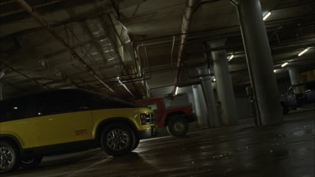 MEDIUM ANGLE OF THREE CARS OR VEHICLES PARKED IN PARKING STRUCTURE OR GARAGE. YELLOW AND BLACK VAN IN FOREGROUND APPEARS TO BE FUTURISTIC. THICK SMOKE OR STEAM FLOWS INTO GARAGE, FILLING MOST OF FRAME. SEE FLAMES OF SMALL FIRE ON GROUND IN BACKGROUND.