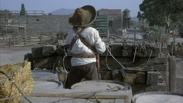 medium angle of cowboy or soldier with bandolier and hand gun. see him on train rail car from behind with pile of wood in front of him. see old western town in background. - bandolier stock videos & royalty-free footage