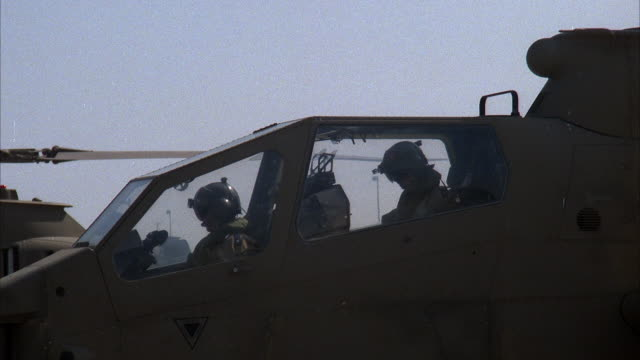 close angle of front or cockpit of cobra military helicopter with two pilots. pans up right to helicopter blade slowly rotating. middle east. attack helicopters. - kampfhubschrauber stock-videos und b-roll-filmmaterial