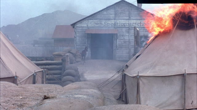 vídeos de stock, filmes e b-roll de medium angle of stable on fire. see beige tents in foreground. see black smoke and fire in front on stable or barn. see desert sand and mountains. see brown horse run out of stable. - barraca