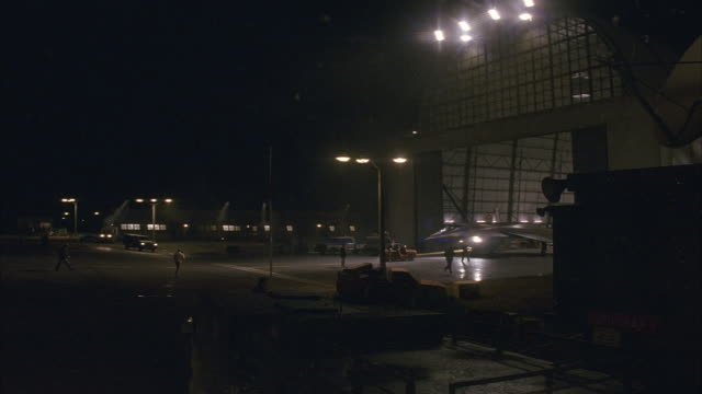 MEDIUM ANGLE OF EMPTY LOT OUTSIDE OF AIRPLANE HANGAR AT NIGHT. SEE MEN WALKING AROUND. SEE BRIGHT LIGHTS. HANGAR DOOR OPENS AND MILITARY JET IS PULLED INTO VIEW.