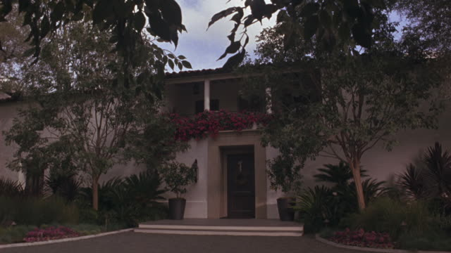medium angle of art deco or spanish style two story house with lots of plants, trees along driveway. windy day, branches swaying.  upper class. dx/nx matching shots. - https stock videos & royalty-free footage