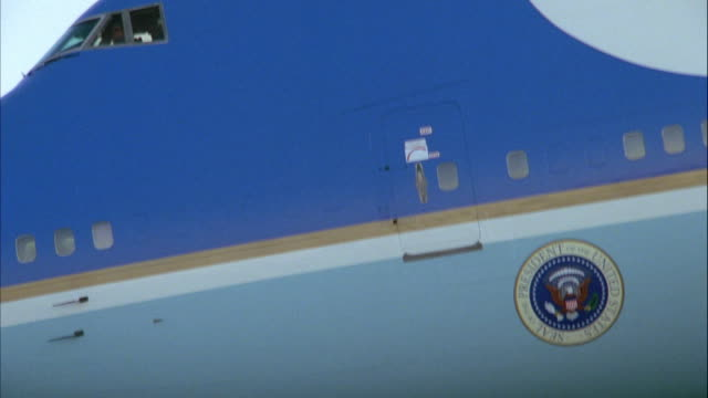 CLOSE ANGLE OF PRESIDENTIAL SEAL ON AIR FORCE ONE JET FLYING ACROSS SCREEN FROM RIGHT TO LEFT. AT END, CAMERA ZOOMS OUT TO SHOW MORE OF JET.