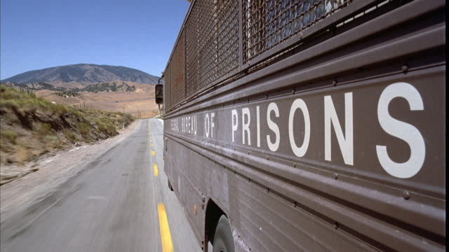 vídeos y material grabado en eventos de stock de medium angle mounted on bus that reads federal bureau of prisons driving along desert road. prison bus. - cárcel