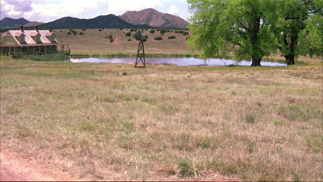 wide angle ranch house and pond in countryside. could be prairie or grassland. windmill. mountains in distance. - ranch home stock videos & royalty-free footage
