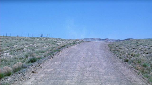 wide angle of desert or prairie landscape. dirt road leading over hillside. could be american southwest, texas, or mexico. - prairie stock videos and b-roll footage