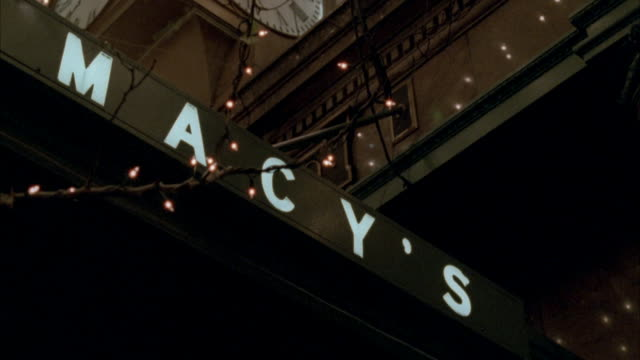 medium angle pan up of macy's department store entrance. pans up to christmas lights decoration. - department store stock videos & royalty-free footage