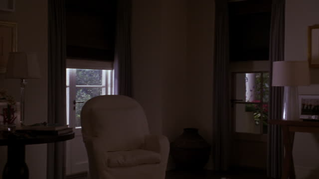 pan left to right of living room in upper class house with windows to trees outside. automatic blinds or shades lower, putting the room into darkness. chairs. - tapparella video stock e b–roll