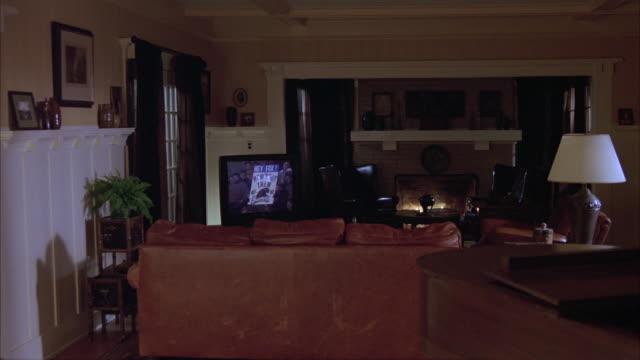 vídeos y material grabado en eventos de stock de wide angle of living room with sofa or couch, fireplace, lamps, piano and television broadcasting football game. - cuarto de estar