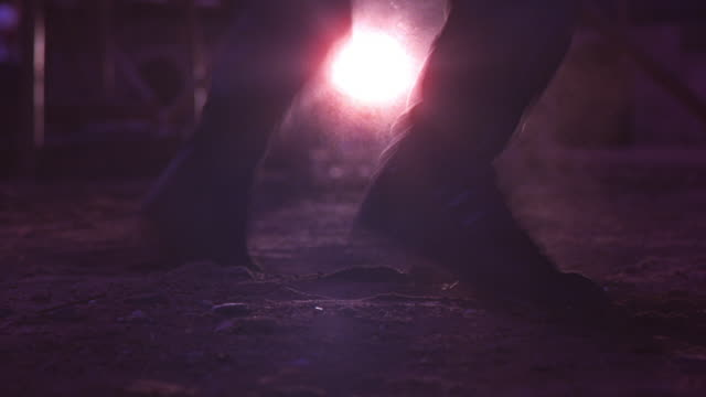 medium angle of boots of man standing in construction area with scaffolds. man jumping in place, his feet land in dirt. series. floodlight in background. - baugerüst stock-videos und b-roll-filmmaterial