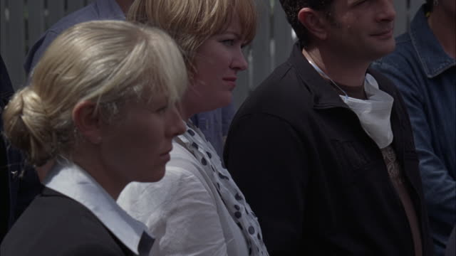 stockvideo's en b-roll-footage met close angle reaction shots of men, women, and children in a crowd. some people wear disposable respirator masks or surgical masks around their necks. - men