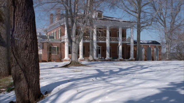 medium angle of rear or back side of mansion with ionic columns. snow blankets ground. some trees in yard, but have no leaves on branches because it is winter. - herrenhaus stock-videos und b-roll-filmmaterial