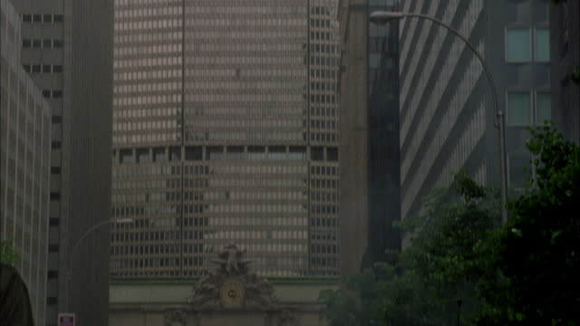 stockvideo's en b-roll-footage met pan down from top of metlife office building to soldiers running down middle of street below. soldiers are looking up to top of building. see rain pouring down. - metlife building