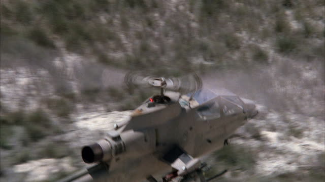 medium angle of top and front of cobra military helicopter flying right. desert with shrubs on ground. middle east. attack helicopters. - attack helicopter stock videos and b-roll footage