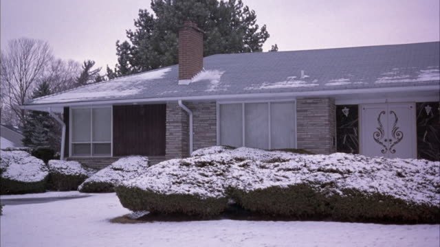 medium angle of middle class one story ranch house. bushes in front with snow and blanket of snow on ground. probably winter. - stereotypically middle class stock videos & royalty-free footage