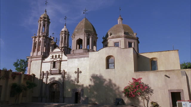 medium angle of exterior of catholic church or cathedral. see beige stucco or adobe walls of building and two domes on top. see two towers in front with crosses on top of roof. - crepe myrtle tree stock videos and b-roll footage