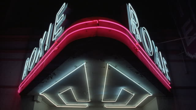 vídeos y material grabado en eventos de stock de pan down of movie theatre from neon sign reading roxie on two sides of marquee, to ticket window. starts with neon sign lit but once lights turn off the camera pans down to dark ticket window. mission district, san francisco. - 1990