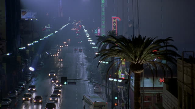 pan l-r along hollywood blvd. see ripley's building then pan right to el capitan theatre. see hollywood blvd. with cars driving in both directions. spotlights in bg. movie theaters. - エルキャピタン劇場点の映像素材/bロール