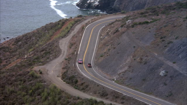 aerial tracking shot of red volkswagen karmen ghia on curvy coastal highway. see ocean to side and cliffs ahead. - volkswagen stock-videos und b-roll-filmmaterial