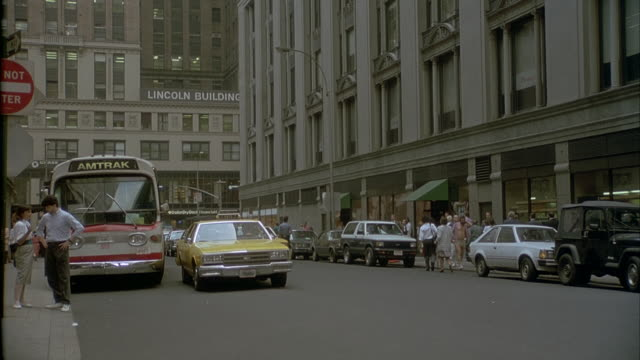 medium angle of alley in new york city. taxi pulls over to left. office buildings on sides. - 1991 stock videos and b-roll footage