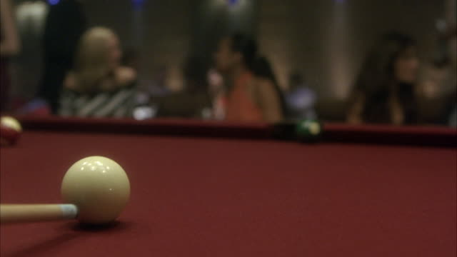 CLOSE ANGLE ON A CUE HITTING CUE BALL ON POOL TABLE IN NIGHTCLUB. BILLIARDS. CUE BALL ROLLS AND HITS GREEN BALL. GREEN BALL ROLLS INTO SIDE POCKET.