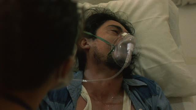 MEDIUM ANGLE OF MAN IN LYING ON HOSPITAL BED WITH OXYGEN MASK. MAN STARTS COUGHING, NURSE GIVES AID.