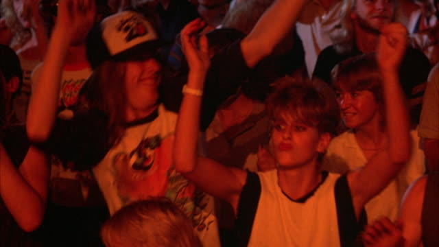 CLOSE UP. YOUNG ROCK CONCERT AUDIENCE IN EARLY 1980'S ATTIRE. YOUNG, LONG-HAIRED MALE DANCES, ACTING VERY ENGAGED IN THE MUSIC. PAN RIGH