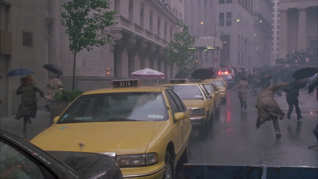 wide angle or people running away frantically from camera in rain. see people holding umbrellas. taxi cabs parked along curb. emergency of state of panic. chaos. pandemonium. - terrified stock videos & royalty-free footage