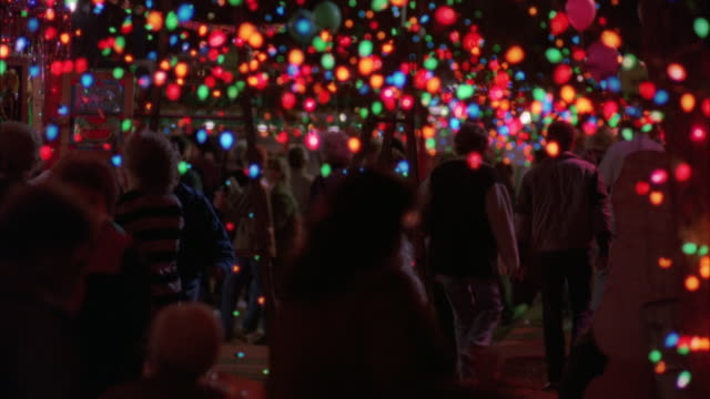 medium angle of dense christmas lights in top foreground. see people sitting on left, people walking in middle, some with balloons. could be fair or art show. neg cut. - louisiana stock videos & royalty-free footage