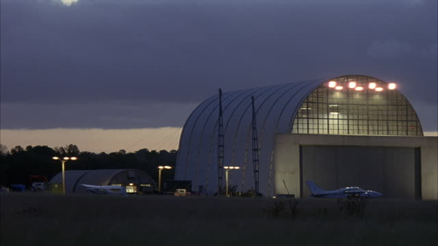 wide angle of hangar in small airport. see small airplane in front of hangar. see field in foreground. dark gray clouds. - 飛行機格納庫点の映像素材/bロール