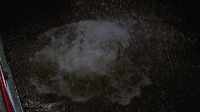 HIGH ANGLE DOWN OF MAN WEARING DRESS SHIRT AND KHAKI PANTS JUMPING OVERBOARD FROM BOAT INTO LAKE PONTCHARTRAIN. WATER SPLASHES. MAN SWIMS AWAY. STUNTS.