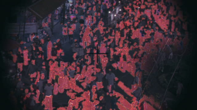 wide angle, rifle scope or binoculars pov of crowds of people. night vision optical effect with a red hue. crosshairs. could be used for snipers, spies, surveillance. - fadenkreuz stock-videos und b-roll-filmmaterial