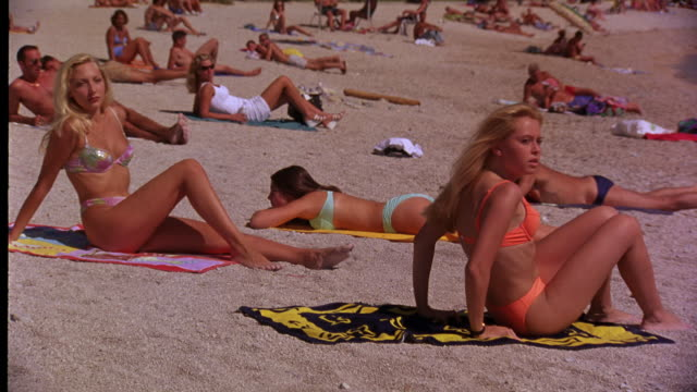 wide angle of sunbathers wearing bathing suits on tropical beach in mediterranean europe. people stand up and begin running away. - swimwear stock videos and b-roll footage