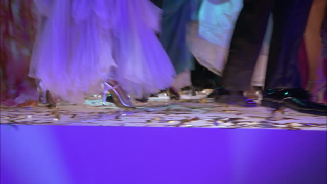 CLOSE ANGLE OF DANCING FEET AT CELEBRATION OR PARTY. CONFETTI ON GROUND. EVENING GOWNS AND TUXEDOS VISIBLE.