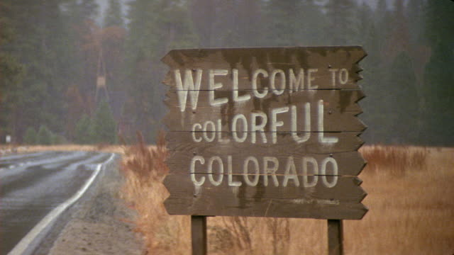 MEDIUM ANGLE OF SIGN THAT READS WELCOME TO COLORFUL COLORADO. BLUE STATION WAGON DRIVES INTO FRAME WITH LUGGAGE LOADED ON TOP.