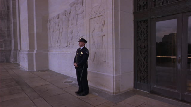 medium angle of front entrance of the capitol building in baton rouge, louisiana.  police officer stands guard in front of marble wall with bas-relief sculpture. government buildings. - marble wall stock videos and b-roll footage