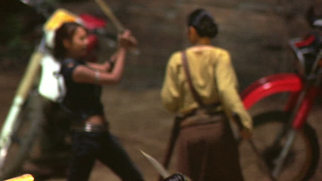 stockvideo's en b-roll-footage met wide angle of men and women fighting with swords dirt area in thailand or asia. see people push and kick each other while sword fighting. see man laying on ground. could be ninjas. martial arts. - krijger
