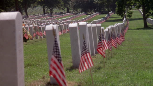 PAN RIGHT TO LEFT OF ARLINGTON NATIONAL CEMETERY. SMALL AMERICAN FLAGS IN GROUND, STICKING UP IN FRONT OF EACH HEADSTONE, PROBABLY FOR MEMORIAL DAY. MILITARY.