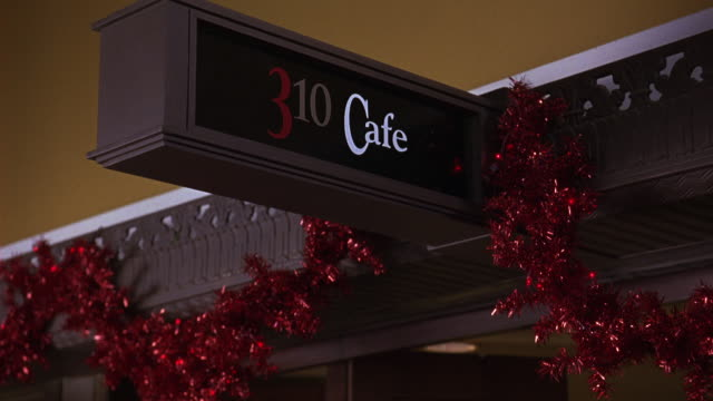 pan down from a sign reading 310 cafe to a woman at a table stirring a drink.  the sign covered in tinsel and christmas decorations.  the woman in the coffee shop or restaurant could be waiting for a date. dating. middle class. - coffee drink stock videos & royalty-free footage