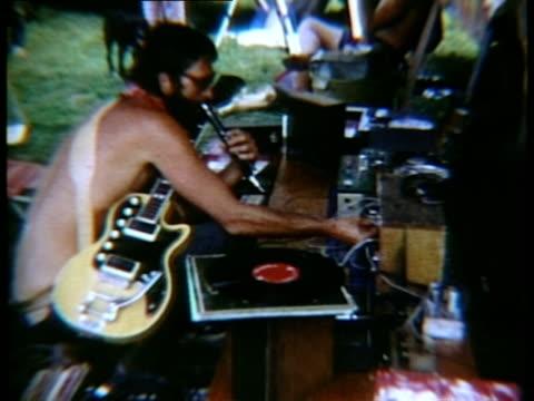 musician adjusting audio system at woodstock music festival/ bethel, new york, usa - 1969 stock-videos und b-roll-filmmaterial