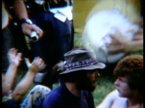 woman playing tambourine and handing it to young boy at woodstock music festival/ bethel new york usa - 1969年点の映像素材/bロール