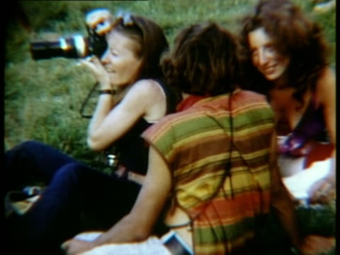 people sitting on grass talking at woodstock music festival/ ms woman taking photograph/ bethel new york usa - 1969 stock videos & royalty-free footage