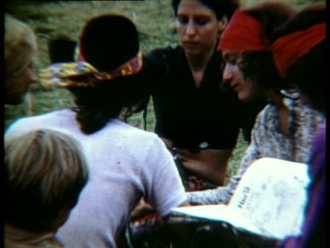 vídeos de stock, filmes e b-roll de group of people sitting on grass smoking at woodstock music festival/ bethel new york usa - 1969